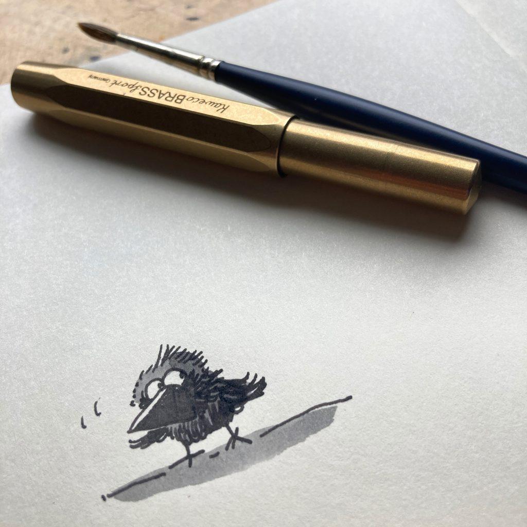 Zeichnung des Rabenkrähenbabys Rrah, der ängstlich nach oben schaut. Über ihm liegen ein Kaweco Sport Füller aus Messing und ein Aquarellpinsel.